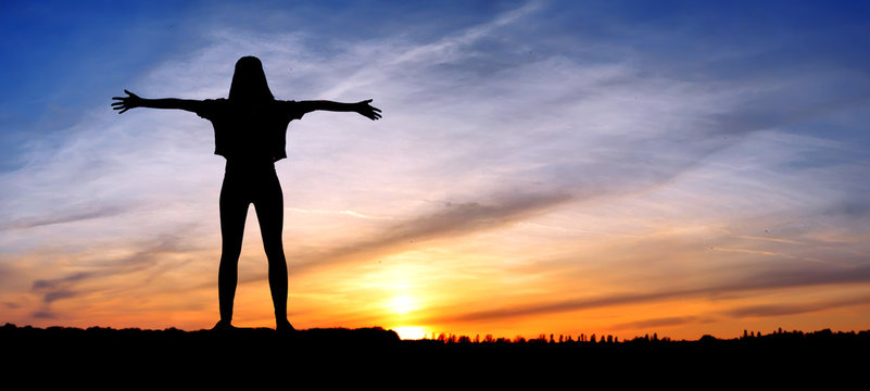 Free happy woman raising arms watching the sun in the background at sunrise, happy girl. silhouette of girl at sunset, jumping on the background of sunset