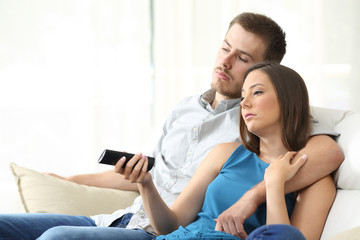 Couple bored watching tv at home