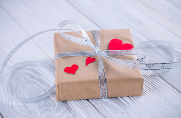 Valentines day gift wrapping on wooden background.