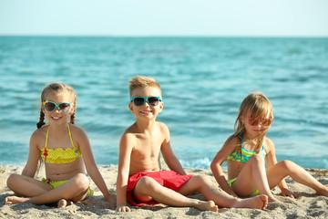 Cute kids sitting on beach sand
