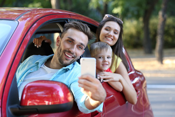 Parents with son taking photo in car on sunny day