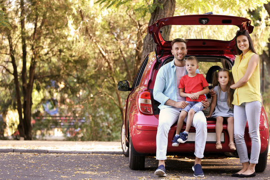Family with kids sitting in car trunk