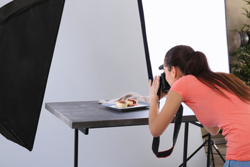 Young woman taking pictures of food in professional photo studio