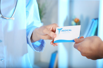 Medical service concept. Female doctor giving visiting card, closeup