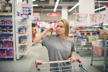 Curious Woman in The Supermarket . Young girl in a market store with  shopping thinking what to buy