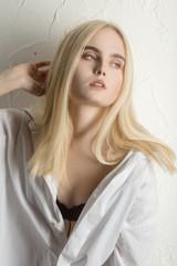 sensual sad blond girl posing near wall