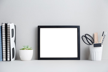 black frame, books and plant on shelf or table.