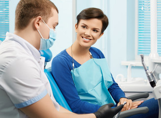 Young female patient visiting dentist office.Beautiful woman sitting at dental chair. Dentist showing dental equipment.Dental clinic.Stomatology..