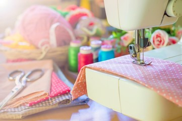 Close up of sewing machine working with pink fabric