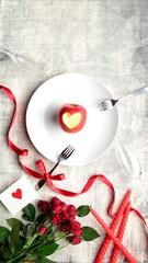 白皿に盛ったハート型に皮を剥いた林檎と赤い薔薇の花束