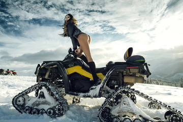 Girl posing on snowmobile outdoors