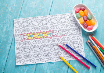 White sheet of paper, coloring for adults for rest and relaxation. Blue vintage background, painted wood. Colour pencils. colored candies in the saucer.