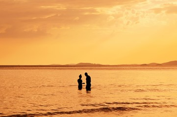 Silhouette of couple in the sea at sunset