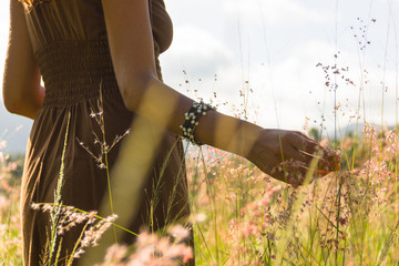 Girl on brown dress and bracelet with pearls walks on a green and yellow grass field softly touching the flowers.