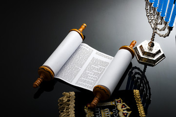 Religion and Judaism concept with the holy Torah and a menorah. The Torah is the jewish holy text / book and a menorah is the traditional branched candle stick specific to Hanukkah Wall mural