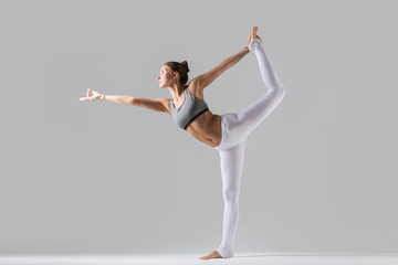 Young attractive woman practicing yoga, standing in Lord of the Dance exercise, Natarajasana pose,...
