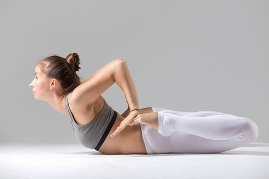 Young attractive woman practicing yoga, stretching in Frog exercise, Bhekasana pose, working out wearing sportswear, white pants, bra, indoor full length, isolated against grey studio background
