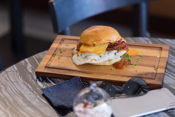 Hamburger, cheese and fried egg is placed on a wooden serving dish.
