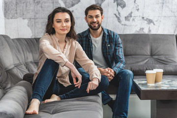 Joyful young man and woman relaxing on couch