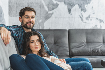 Young man and woman sitting on couch