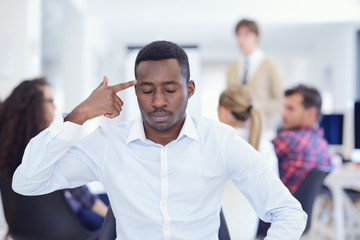 Furious black businessman tired of working on project at office.