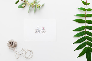 Postcard with bicycle and herbarium flat lay. Top view on handmade greeting card with green leaves and twine ball. Handmade decoration, art, craft, hobby concept