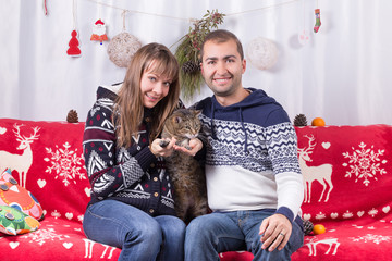Happy couple and their cat sitting on a sofa with festive decorations and celebrating