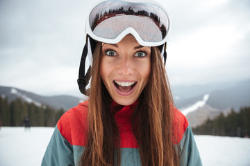 Young excited happy lady snowboarder on the slopes