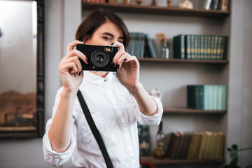 Pretty Authoress making photo on retro camera