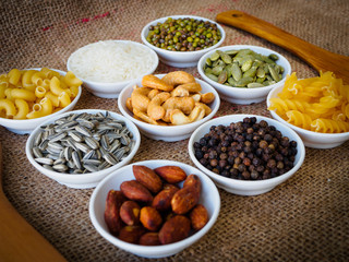 Almond, black pepper seed, Sun flower seed, Cashew nuts, Pumpkin seeds, green bean, rice, fettucine, all put on small white cup and on brown hemp sack texture background