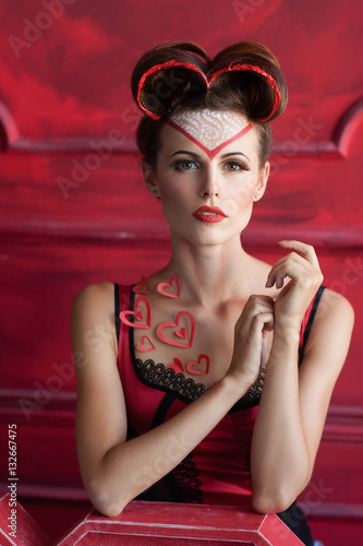 67109c4a14 Serious beautiful woman with hearts decorations. Pensive girl in red  lingerie with bright makeup looking