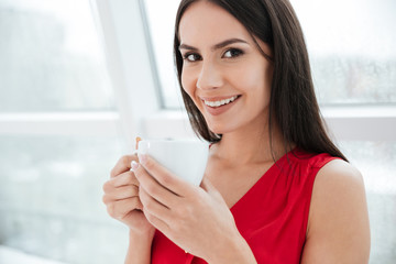 Close up smiling woman with cup of coffee in office