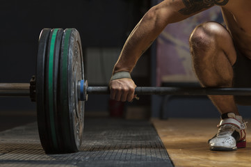 Sporty young man with naked torso lifting barbell