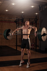 Strong muscular man lifting barbell in gym