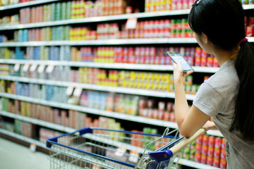 Woman using phone in supermarkets check to buy