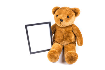 Brown fuzzy teddy bear holding a black frame isolated on a white background
