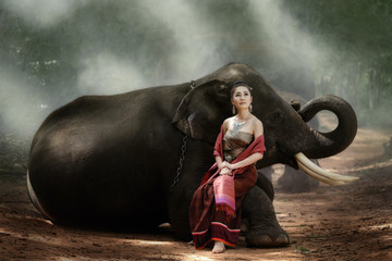 Beautiful asian woman sit on elephant with Thai culture traditional dress.