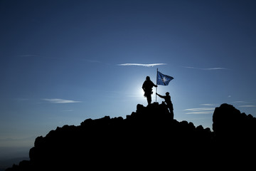 Two soldiers put the NATO flag on top of the mountain