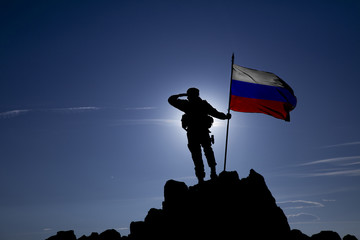 soldier on top of a mountain with a Russian flag