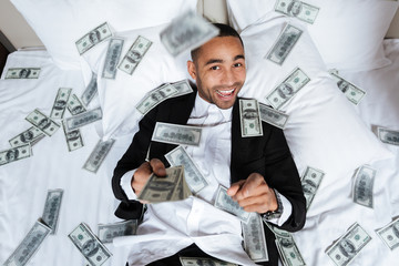Smiling African man lying on bed with falling money