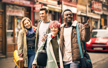 Happy multiracial friends walking on Brick Lane at Shoreditch London - Friendship concept with multicultural young people on winter clothes having fun together - Soft focus with dark contrasted filter