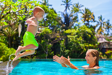 Happy child in action - active kid swim with fun in swimming pool. Baby son jump high to mother catching hands. Healthy family lifestyle, summer vacation water sports activity and lessons with parents