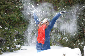 Portrait of young woman throwing the snow, outdoors. Smiling girl walking in a winter park and having fun on a cold sunny day.