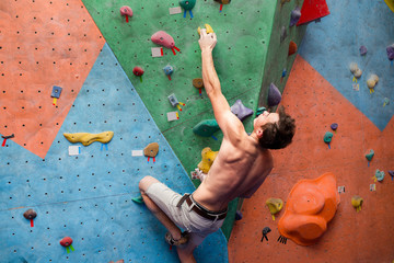 Handsome muscular naked shirtless climber at gym wall
