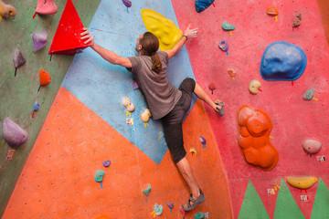 young man climbing artificial boulder indoors, modern sport concept