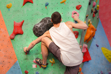 Strength and sporty male climbing on an indoor climbing wall.