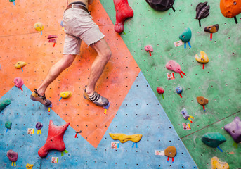 Close-up image of male foot on climbing wall with copy text space