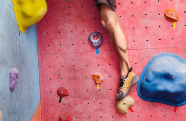 male climber training in bouldering gym wall, close up of leg muscles with shoes