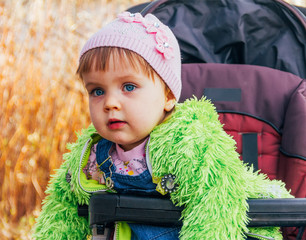 portrait little girl with blue eyes in pink cap and green jacket, tinted photo