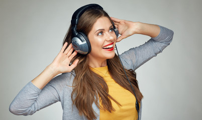 happy dancing woman with headphones isolated on gray background